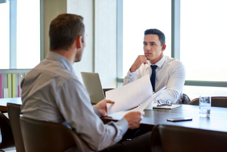 two men discussing in a meeting | Kenneth M. Sigelman & Associates | San Diego, CA